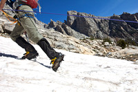 A student climbing the snow covered Teton Mountains during a mountaineering trip.