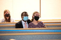 A couple wearing face masks sits and watches General Conference in the Taylor Chapel.