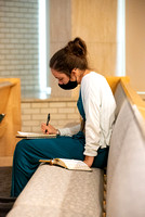 A student wearing a face mask takes notes during General Conference.