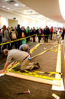 Campus faculty glues together the frame that will encompass a new mural in the I-Center Lobby.