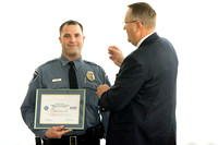 Garth Gunderson, University Security and Safety Director present a pin representing his award to Bryan Lyons.