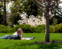 Student Chloe Beaudoin does some homework on the grass on campus.