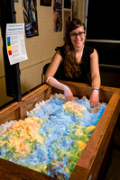 The topographical sandbox uses an Xbox Kinect sensor to project a virtual topographical image onto the sand. It uses different colors to show elevation changes and adjusts the image as patrons interac