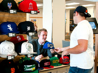 Kellen Heiner, student from the IBC Business Class talks with Erick Green, a student at BYU-Idaho, about buying a baseball cap in the MC Building.