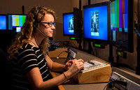 McKenzie Marcum sitting at the controls in the camera control room in the BYU-Idaho Center.