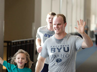 An employee of BYU-Idaho and participant in the Try-A-Tri, waves to a video camera as they run past.