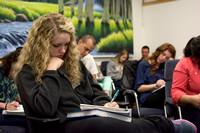 A student takes notes as she listens to Brother Clay talk about the self-serving bias.