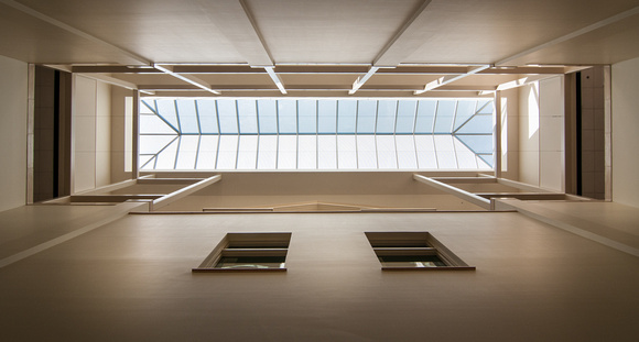 Skylights stream in natural light illuminating art and photography in the hallways of the Jacob Spori Building.