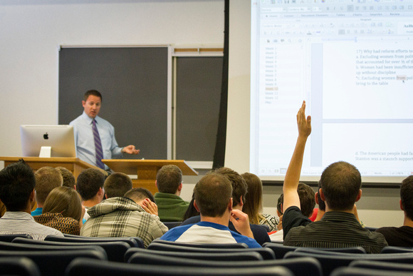 A student raises his hand to ask Brother Hyrum Lewis a question while he teaches American Foundations during the 2014 Spring Semester.
