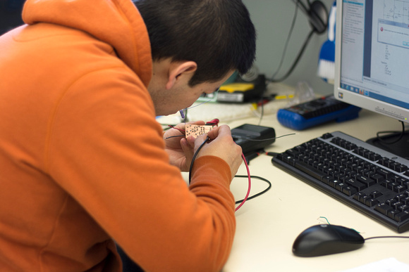 An Electrical Engineer student solders on an electrical component.