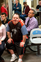 Volunteers assist (or are assisted) and cheer on bowlers in an Adaptive PE class.