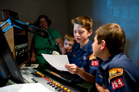 Webelo scouts get to try their skills in the production room while taking a tour of the radio station.
