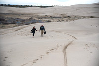 Emily Gottfredson and Mike hike up the Sand Dunes for the University Relations Photographer Group Shot.
