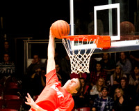 A student making an amazing one-handed basketball dunk.