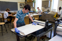 A student in Sister Jimison's Printmaking class, prepares to use the press for an assignment.