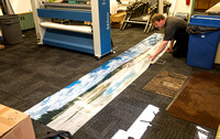Darrell Holmes alligning a 14 foot panoramic print of Norris Geyser Basin for the Teton Geotourism Center in Driggs, ID.