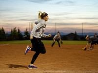 A recreational softball player sprints towards first base.
